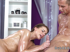 Nude oiled masseuse giving handjob to customer