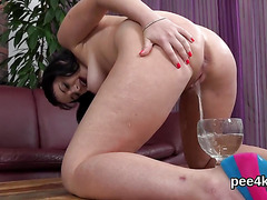 Charming cutie is pissing and rubbing shaven snatch