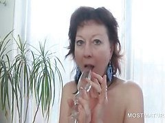 Appealing mature fucks hot pussy with glass dildo