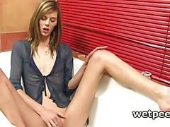 Skinny girl pissing in bathtub plays with wet pussy