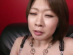 Rio Kagawa is squeezing her tits and playing with her pussy on a black leather chair