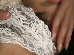 Lovely Maki looks great in white lace and thigh high stockings as she toys her pussy with a hangar