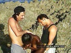 Horny black babe sucks off 2 big white rods at the beach